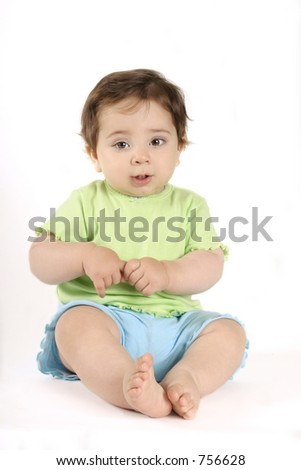 Sitting baby in lime t-shirt and aqua shorts casual on white.