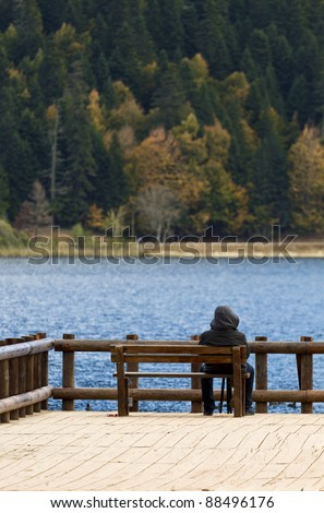 Sitting bench by the lake alone - stock photo