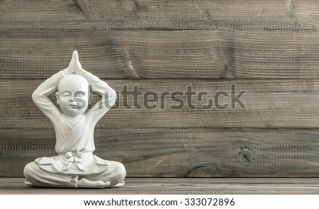 Sitting buddha. White monk statue on wooden background. Meditation. Relaxing. Retro style toned picture - stock photo