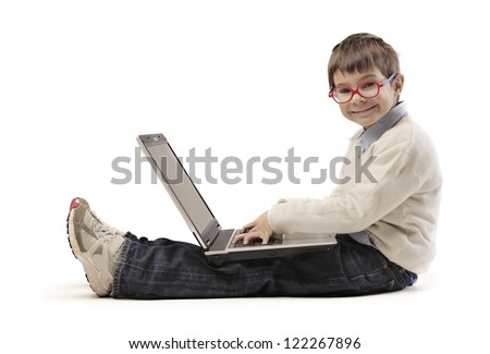 Sitting child with red glasses using a laptop computer - stock photo