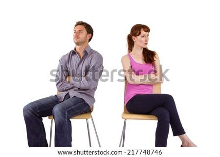Sitting couple ignoring each other on white background - stock photo