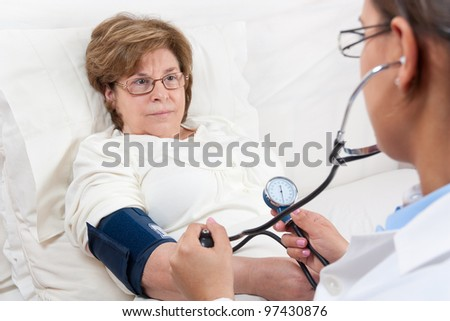 Sitting Doctor is measuring the Blood Pressure on a Senior Patient - stock photo