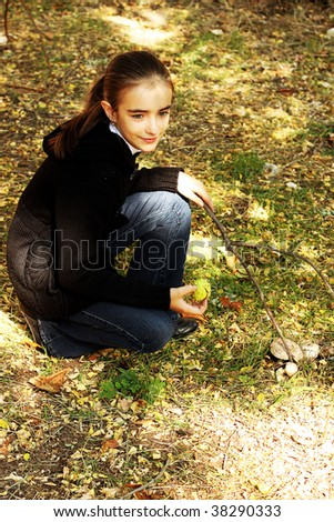 Sitting girl in the forest. Collecting mushrooms.