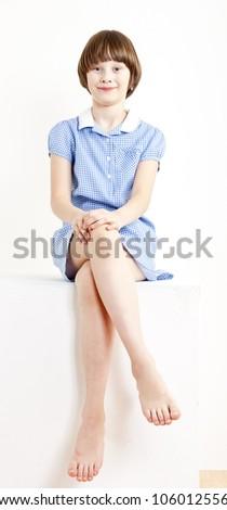 sitting girl wearing blue dress - stock photo
