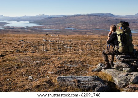 sitting Hiker with heavy backpack in Lapland - stock photo