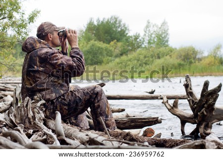 sitting hunter  looks through the binoculars on the river - stock photo