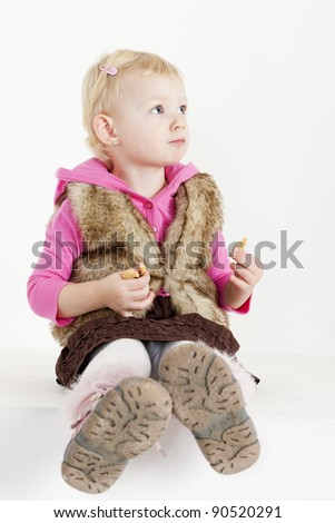 sitting little girl holding cookies - stock photo