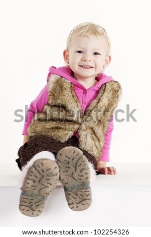 sitting little girl wearing vest - stock photo