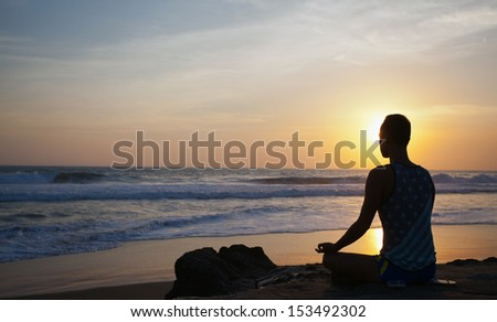 sitting man doing yoga on shore of ocean, bali, indonesia