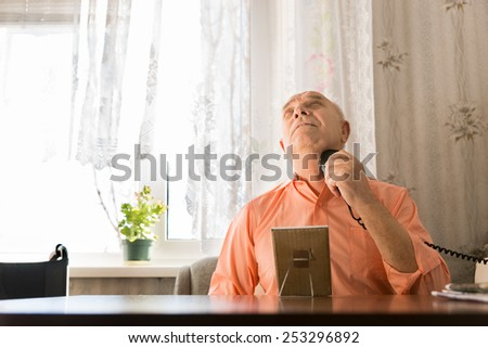 Sitting Old Man in Orange Shirt Shaving Hairs on his Neck Using Electric Razors While Facing Up - stock photo