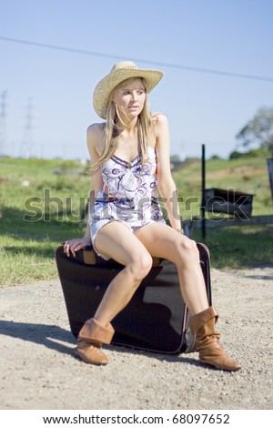 Sitting On A Suitcase On A Dusty Country Road A Backpacker Woman Smiles In Happiness For She Is On A Dream Outback Holiday - stock photo