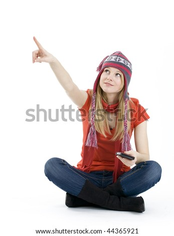 sitting on the floor smiling girl from crossed legs in winter cap pointing - stock photo