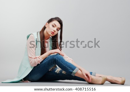Sitting portrait young brunette girl wearing in pink blouse, turquoise jacket, ripped jeans and cream shoes .Fashion studio shot on gray background - stock photo