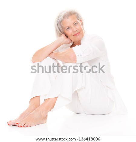 Sitting senior woman in front of white background - stock photo