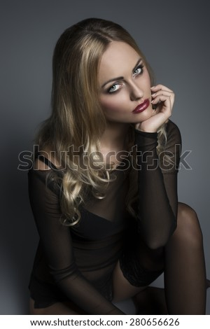 Sitting sexy girl with transparent shirt, black lingerie and stockings posing with long blonde wavy hair,. stylish make-up and charming sad expression  - stock photo