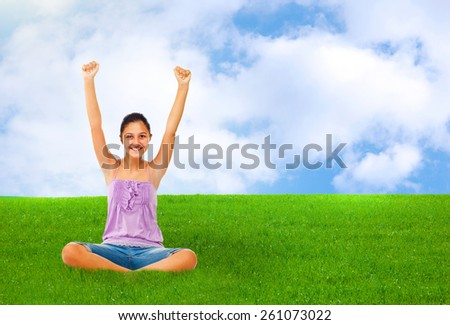 Sitting teenage girl while rejoices with arms up in green grass with blue sky. - stock photo