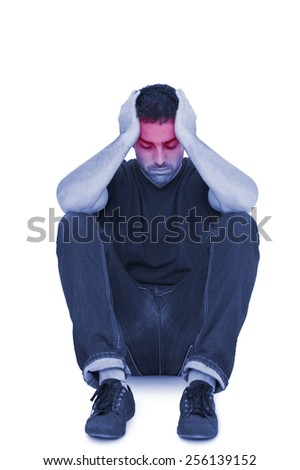 Sitting upset man with head between hands on white background - stock photo