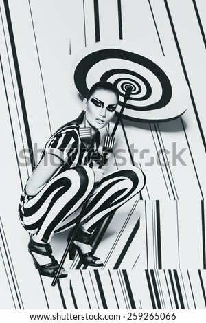 sitting woman in striped costume on striped background in studio - stock photo