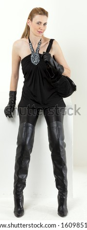 sitting woman wearing black clothes with a handbag - stock photo