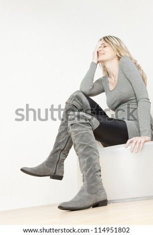sitting woman wearing fashionable gray boots