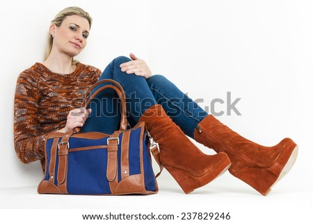sitting woman wearing fashionable platform brown shoes with a handbag - stock photo