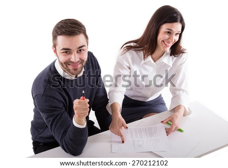 sitting young man showing his pencil to camera, while young woman showing to him where to sign - stock photo