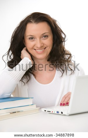 sitting young woman with books and laptop - stock photo