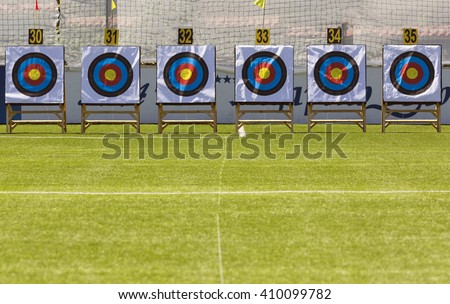 Six archery target rings during an archery competition. Green grass. - stock photo