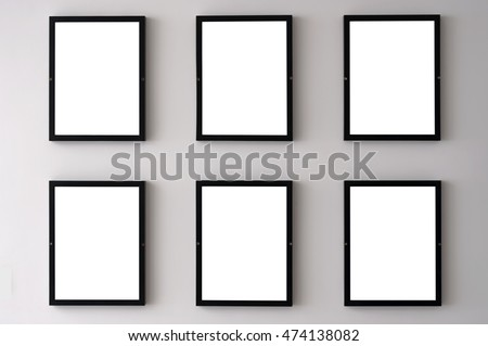 Six blank picture frames hanging on a white wall.