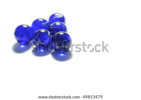 Six blue marbles arranged in a triangle shape on a clean and neat white background with some space on the right. - stock photo