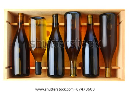 Six bottles of Chardonnay wine in a wooden case, view from above over a white background. - stock photo