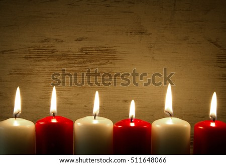 Six burning candles, three red and three white along the bottom edge with copy space at the top. Interesting festive background, frame. Horizontal view.