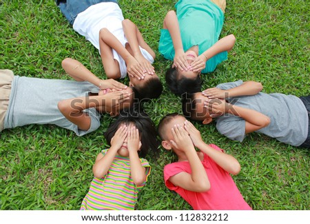 Six children cover their face with green glass background. - stock photo
