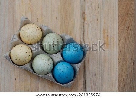 Six colored easter eggs on a wooden surface. The speckled eggs are in a carton. They are in pastel shades of yellow, green and blue. There is copy space on the right side of the image. - stock photo