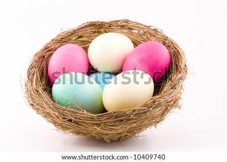 Six colorful dyed Easter eggs snuggle in a birds nest. - stock photo