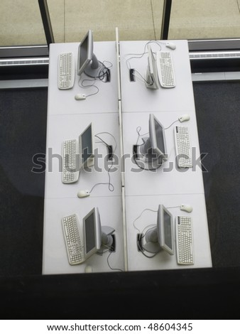 Six computer terminals in student center of community college - stock photo