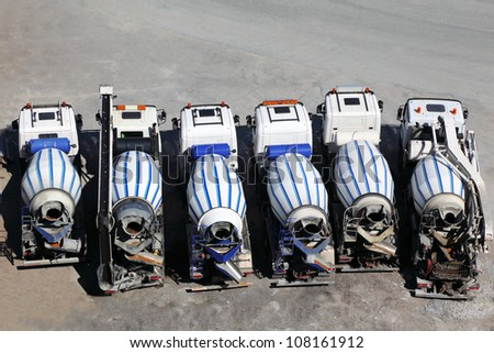 Six concrete mixer machines stand on asphalt at sunny day; back view - stock photo