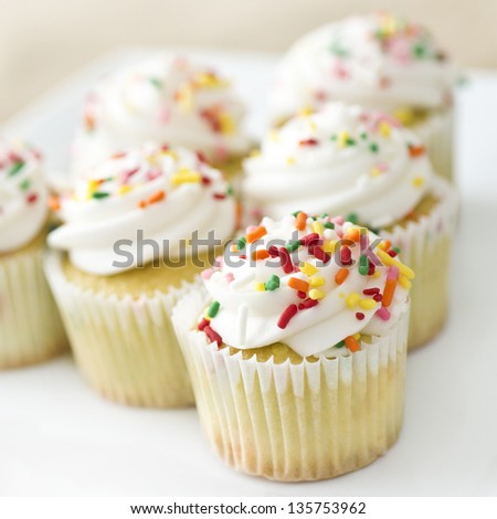 six cupcakes with rainbow sprinkles - stock photo