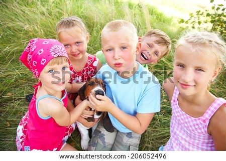 Six cute children playing with dog  at summertime