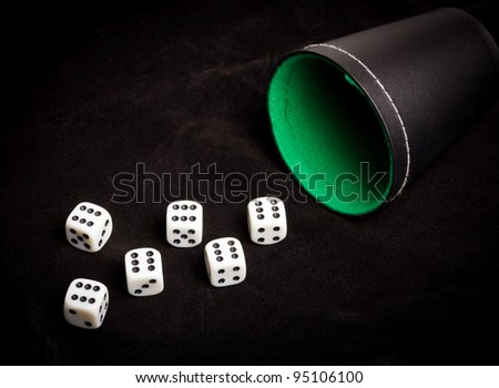 Six dice with number six facing up on black board - stock photo