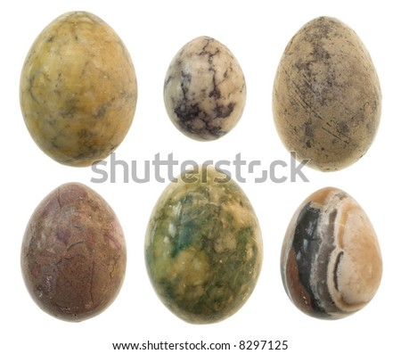 Six different sized marble eggs arranged on white background