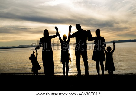 six family member at beach silhouette sunset