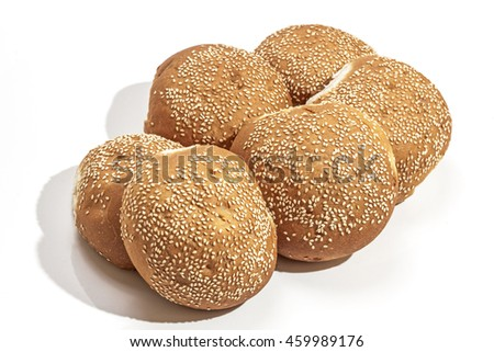 Six freshly baked crisp golden hamburger rolls sprinkled with sesame seeds on white background