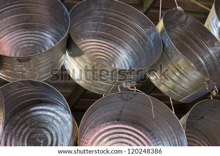 Six galvanized steel wash tubs hang from the rafters and fill the frame. The shiny, new tubs can be used for washing and are traditional symbols of poverty. - stock photo