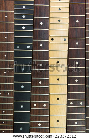 Six guitar necks aligned, Rosewood, maple and ebony fingerboard necks  - stock photo