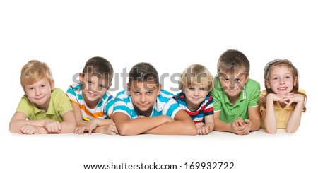 Six happy children are lying on the floor on a white background