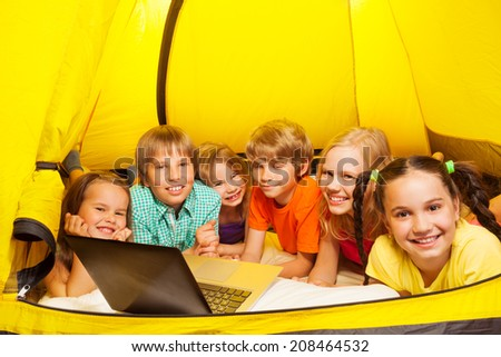 Six kids lay in a yellow tent - stock photo