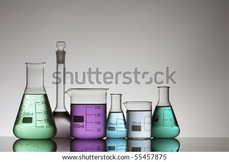 six laboratory flasks on a white backlight