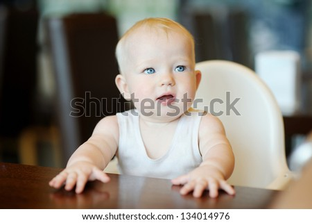 Six month old baby girl sitting by the table - stock photo