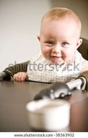 Six month old baby in high chair ready to eat